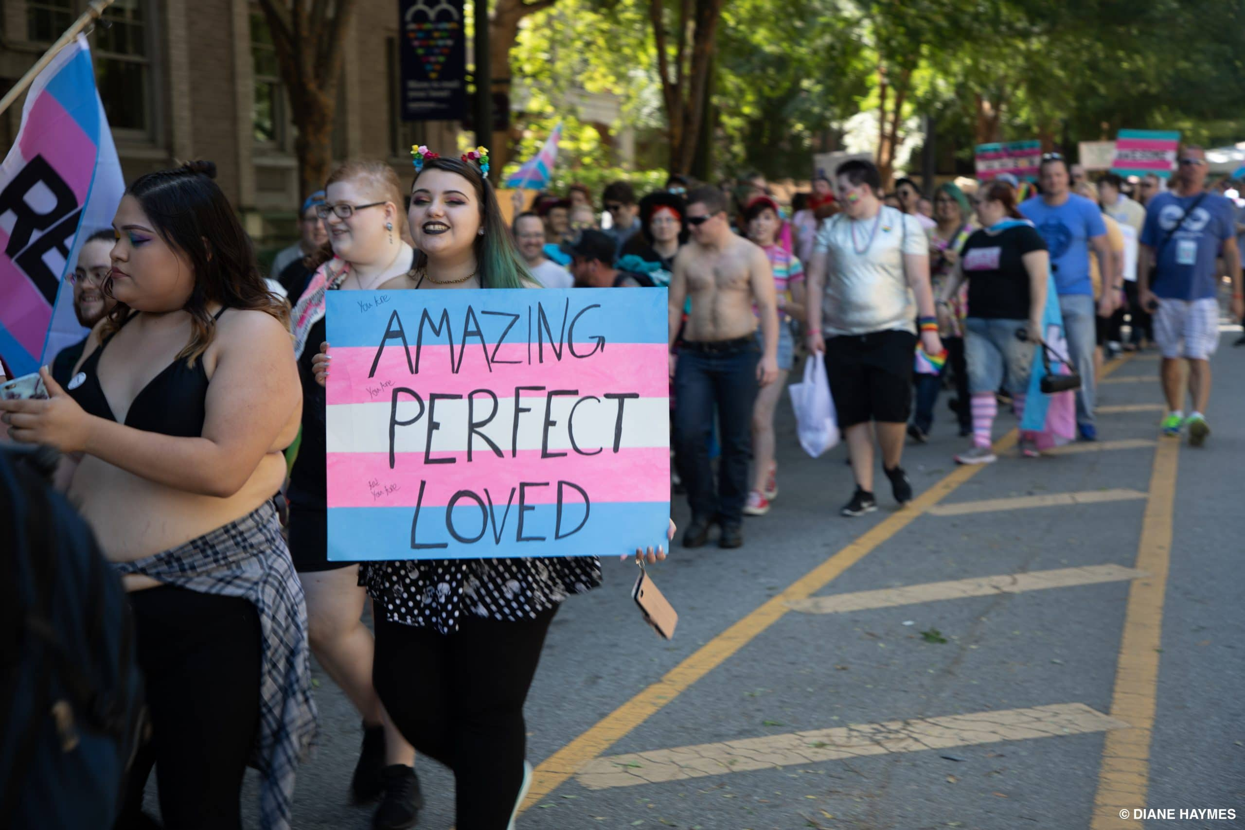 Trans march attendees of Atlanta Pride 2018, carrying signs and banners of trans colors and messages of empowerment.