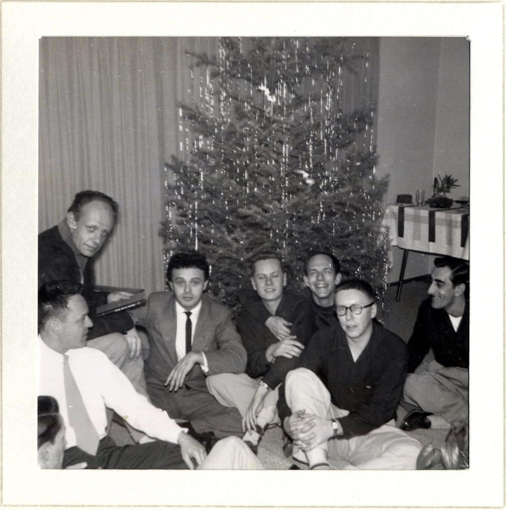 Seven members of the Mattachine Society--dressed in suits and business casual wear--pose in front of a Christmas Tree. Two of the men embrace.