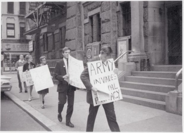 5 protestors, each holding signs, march on the sidewalk. One sign reads: ARMY INVADES SEXUAL PRIVACY