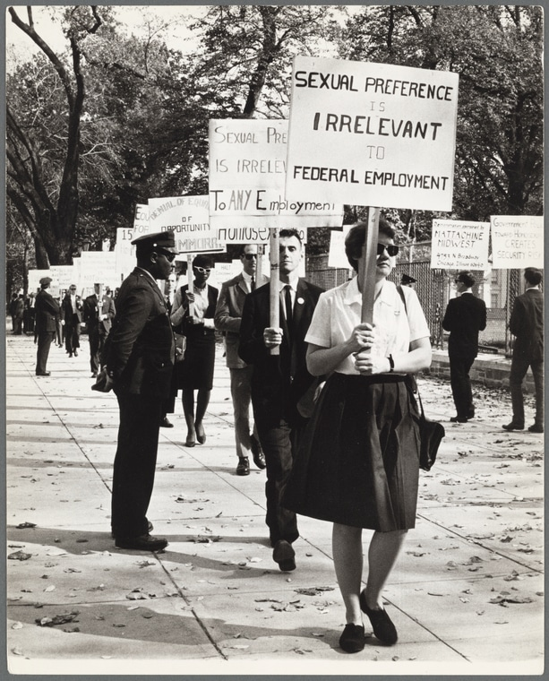 "Barbara leads a group of protestors on the sidewalk. Her sign reads ""Sexual Preference is Irrelevant to Federal Employment."""
