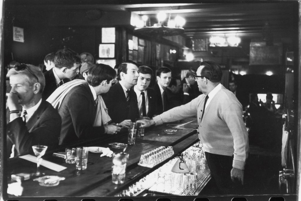 A bartender holds his hand over a drink of one of the several men lined up as part of the sit-in.