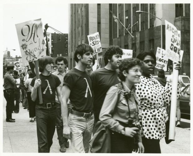 "A group of protestors gather along the sidewalk. One man holds another around the waist, a sign reads ""Gay is good."" One woman holds a camera."