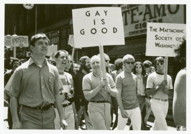 A group of protestors march along the sidewalk. A male's sign reads GAY IS GOOD.