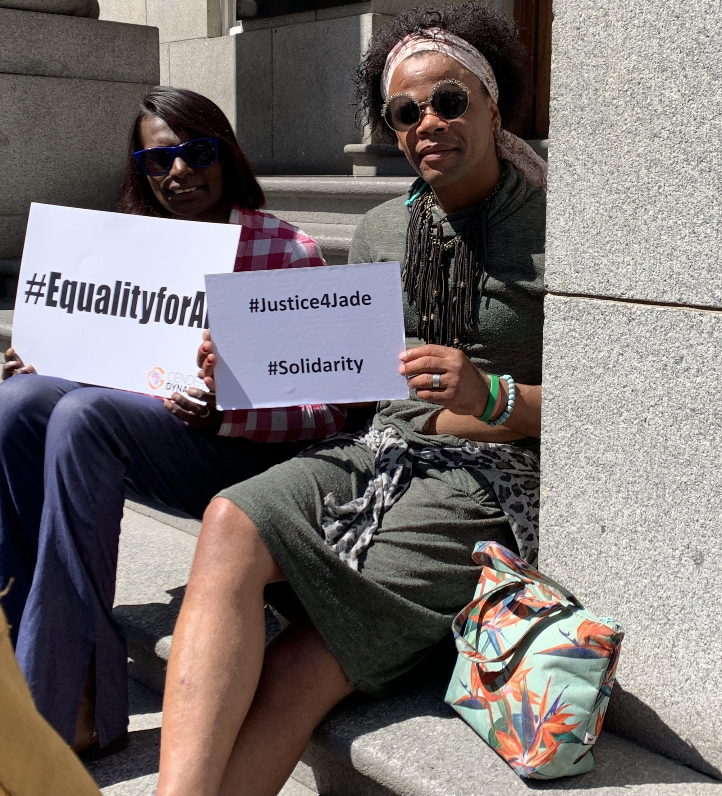 Two protestors sit on the courthouse steps holding signs that read, '#EqualityforAll' and '#Justice4Jade #Solidarity'.